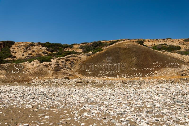 Stena inskrivna handstilar och förälskelsehjärtor på en kulle på den Aphrodite Rock stranden i Cypern fotografering för bildbyråer