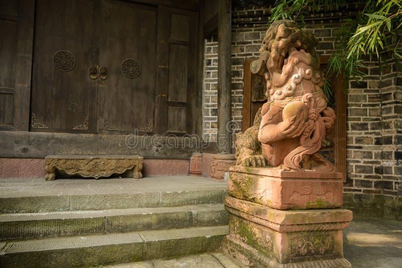Stena lejonet på porten av den forntida kinesiska herrgården på solig dag royaltyfri foto