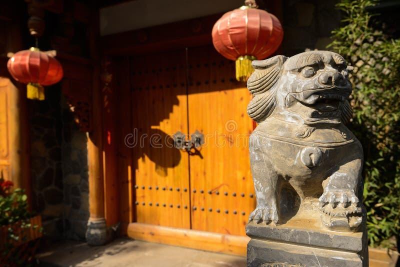 Stena lejonet på porten av kinesisk traditionell byggnad i solig afte arkivbild