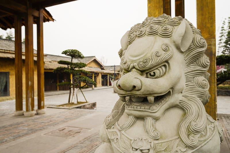 Stena lejonet på porten av kinesiska traditionella byggnader i eftermiddag royaltyfria bilder