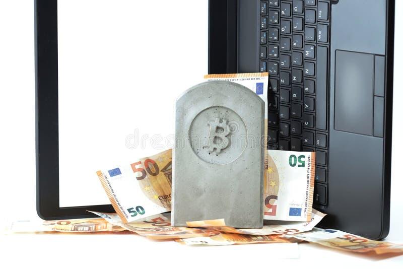 stena monumentet/gravstenen med bitcoinsymbol på en hög av sedlar framme av anteckningsboken royaltyfri fotografi