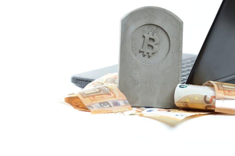 stena monumentet/gravstenen med bitcoinsymbolanseende på en hög av sedlar framme av en svart anteckningsbok på vit bakgrund arkivfoto