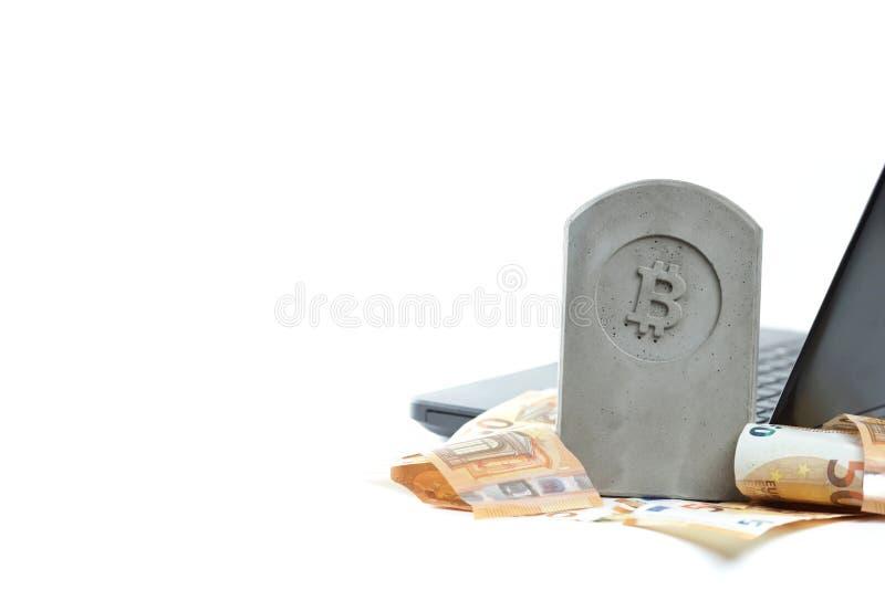 stena monumentet/gravstenen med bitcoinsymbolanseende på en hög av sedlar framme av en svart anteckningsbok på vit bakgrund royaltyfria bilder