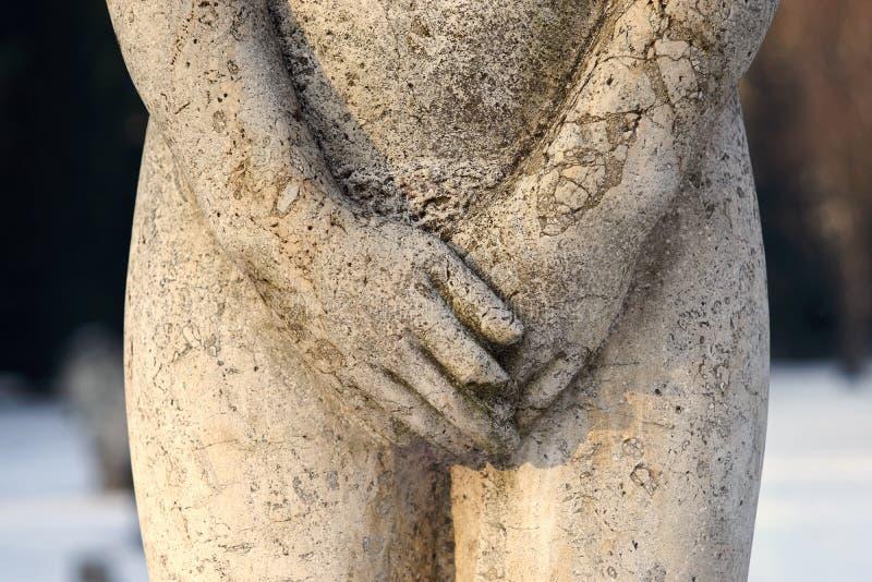 Stena skulptur, kvinnliga könsdelar som täckas med händer, closeup royaltyfri fotografi