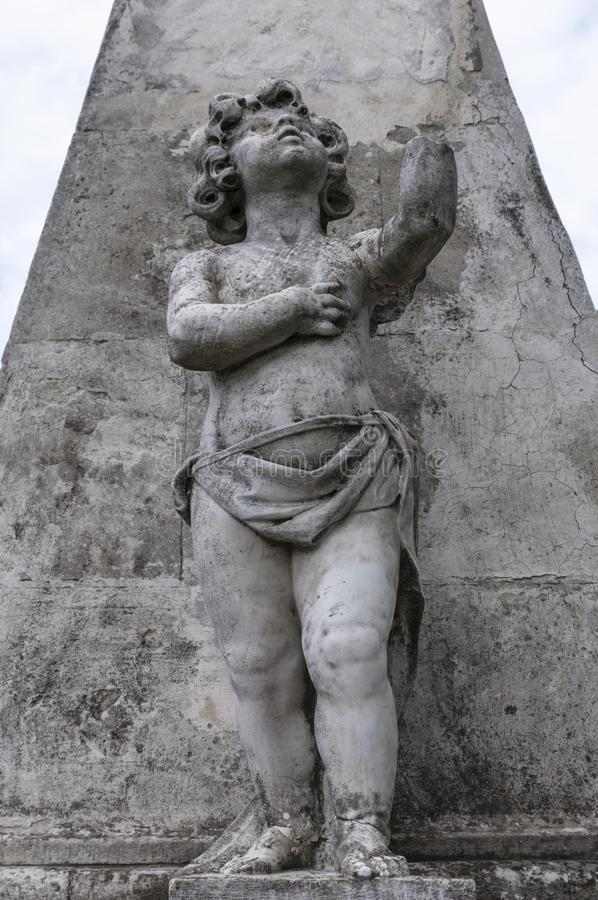 Stena statyn av ett barn på en sockel royaltyfria bilder