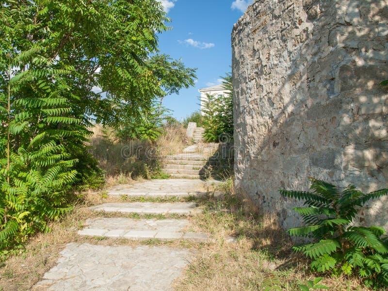 Stena trappa tillsammans med av steniga väggar av en forntida fästning in royaltyfri foto