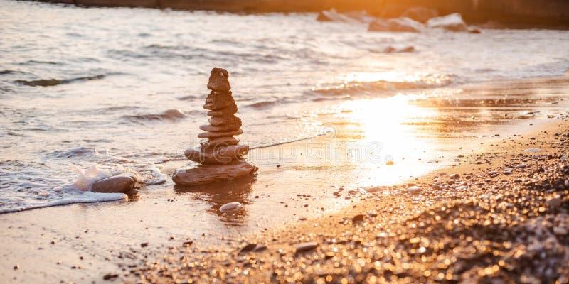 stenar av pyramiden på stranden symboliserar begreppet av zenen, harmoni, jämvikt royaltyfria bilder