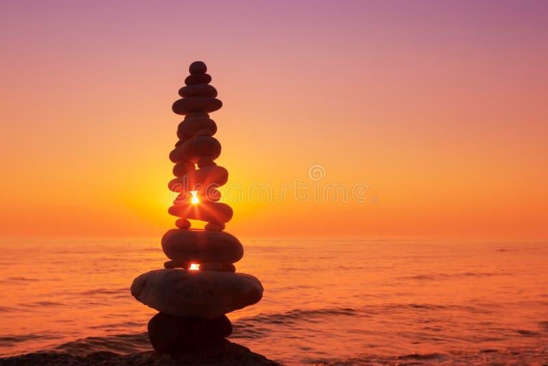 Stenar balanserar på en bakgrund av havssolnedgången härligt ligga för holding för harmoni för green för gräs för flicka för begr royaltyfria bilder