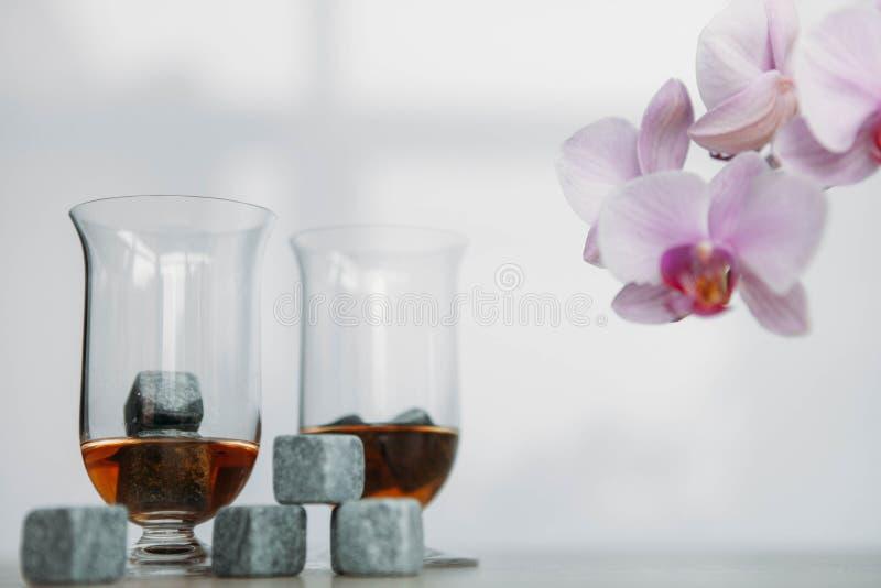Stenar för att kyla whisky- och glasestulup på ljus träbakgrund royaltyfri bild
