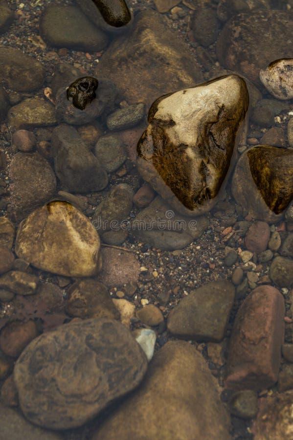 Stenar i floden som utom fara fotograferas från ovannämnt/klart flodvatten och det färgrika stones/fotoet av floden /Backgroun fö arkivfoto