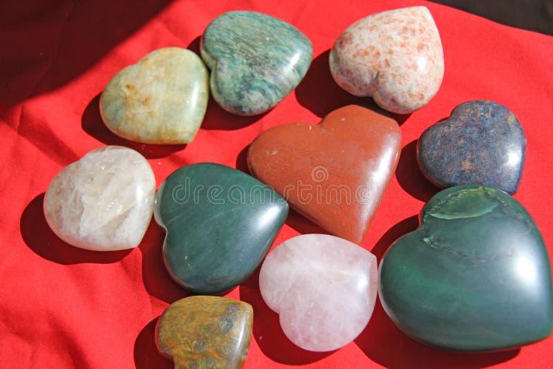 Stenar i formen av hjärta ligger på en röd bakgrund Hjärta som göras av den naturliga kvartsstenen, rhodochrosite, jade, aventuri arkivbild