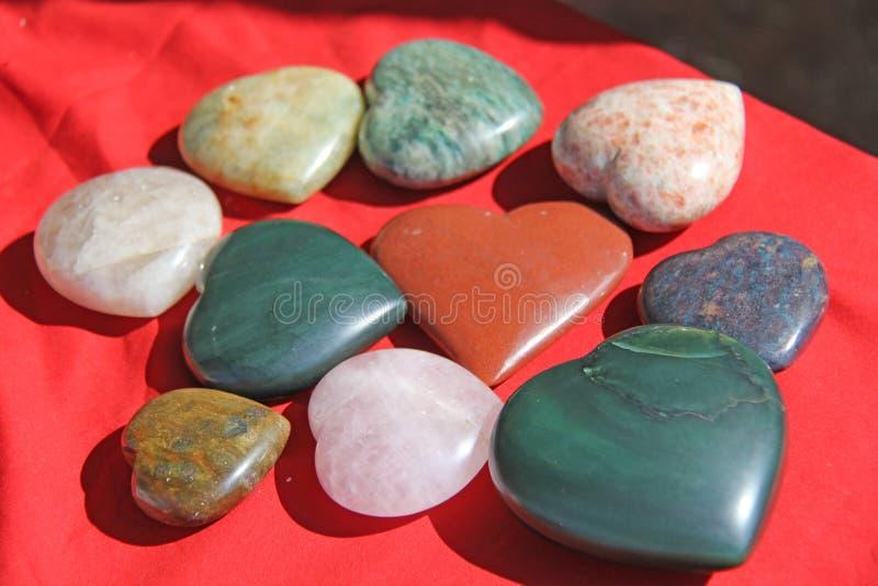 Stenar i formen av hjärta ligger på en röd bakgrund Hjärta som göras av den naturliga kvartsstenen, rhodochrosite, jade, aventuri royaltyfria foton