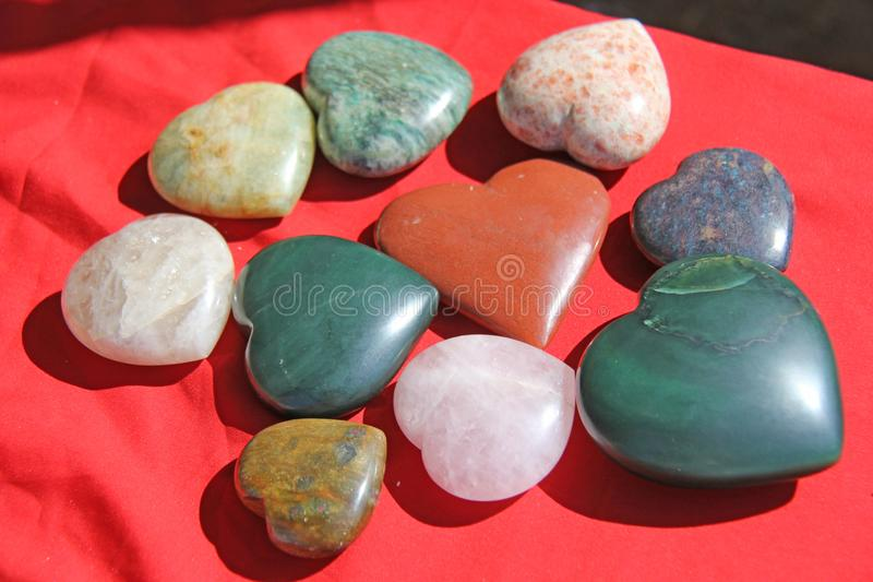 Stenar i formen av hjärta ligger på en röd bakgrund Hjärta som göras av den naturliga kvartsstenen, rhodochrosite, jade, aventuri royaltyfri bild