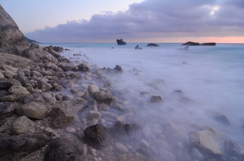 Stenar i mjölkaktigt vatten arkivbilder