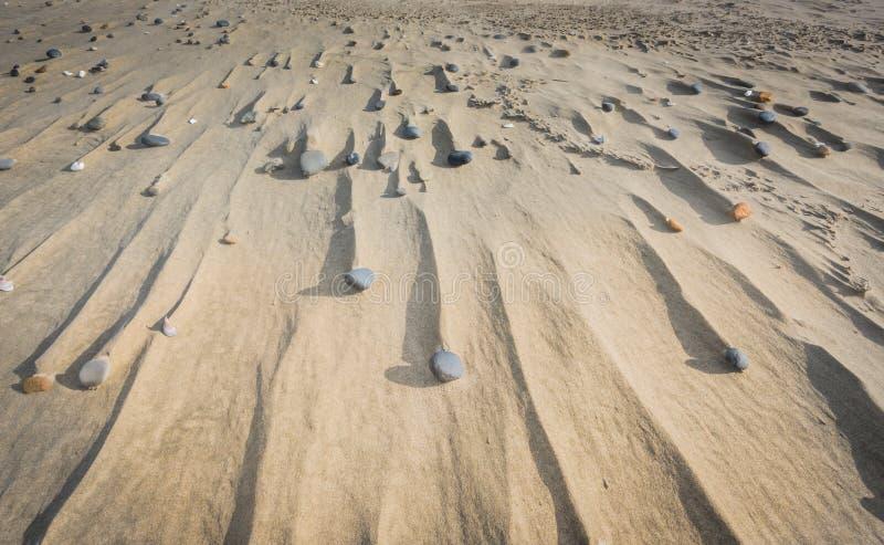 Stenar och drivor i sand arkivfoto