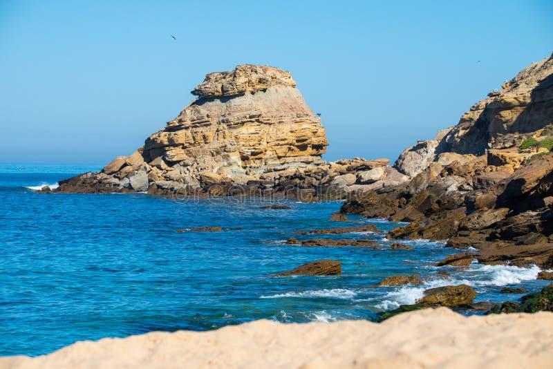 Stenar och vaggar på en strand under himmel blåa Atlantic Ocean mot klipporna under solig dag royaltyfri bild