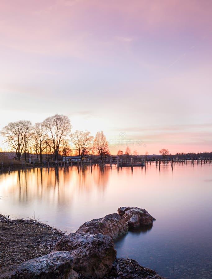 Stenar på en sjö under solnedgång fotografering för bildbyråer