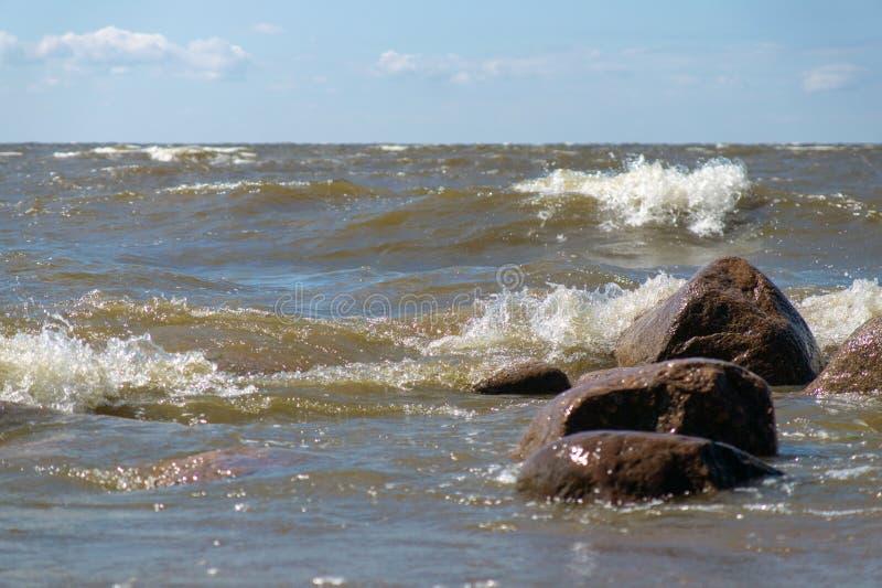 Stenar på havsstranden som tvättas av vågorna arkivbilder