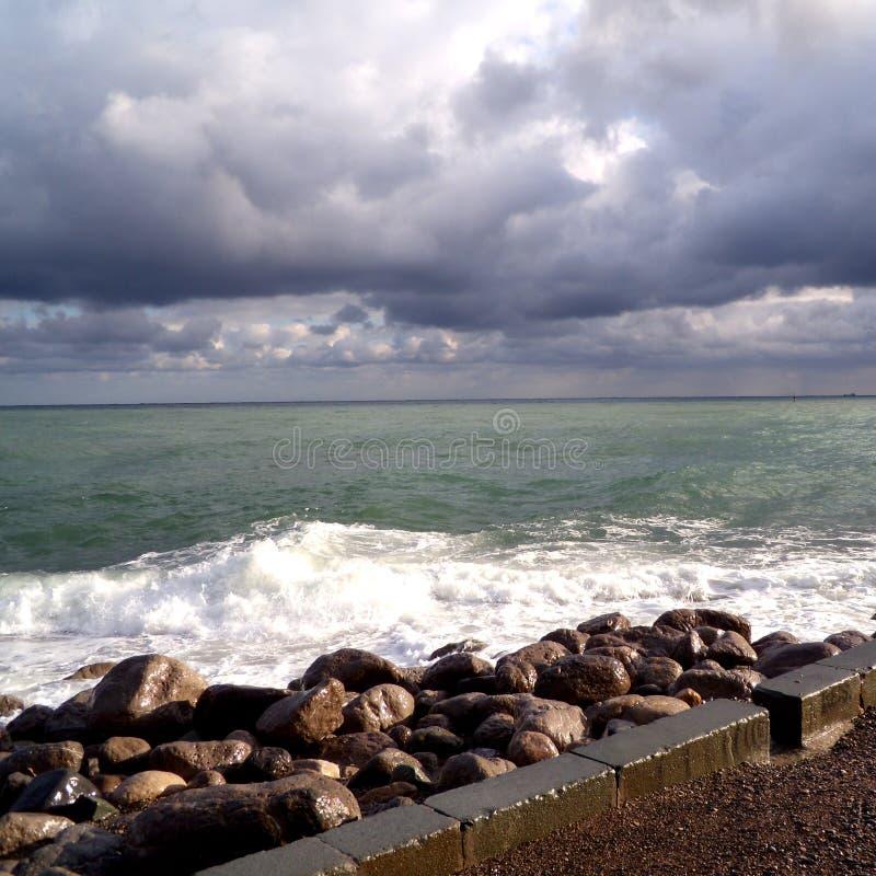 Stenar på invallningen Besk?da av stormseascape M?rk lynnig himmel ?ver det gr?a havet Vågor och mörka moln i stormig dag arkivfoto