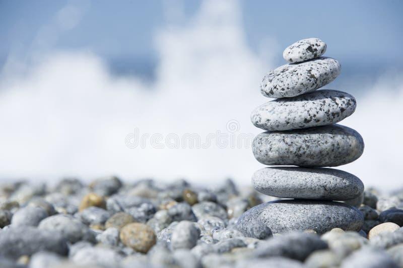 Stenar pyramiden på Pebble Beach som symboliserar brunnsortbegrepp med suddighetshavsbakgrund royaltyfri fotografi
