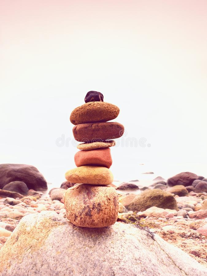 Stenar pyramiden som symboliserar zenen, harmoni, jämviktskiselstenar Hav i bakgrund arkivbild