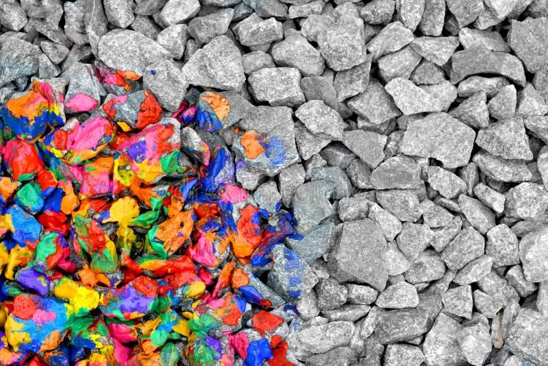 Stenar som färgas i olikt färgfärgpulver på halvan, andra halvan - monokromgrå färgstenar royaltyfria foton