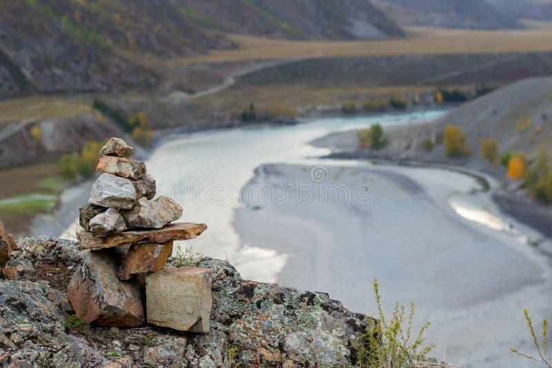 Stenar staplade glidbanan överst av de i en turist- pittoresk bergskedja i en dal med en turkosflod royaltyfria bilder