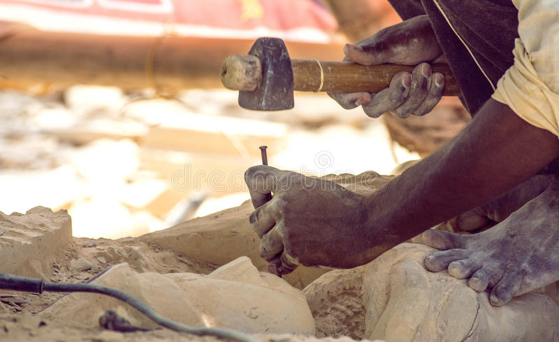 Stenarbetarhänder som snider stenen royaltyfri bild