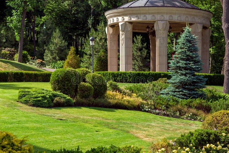 Stenaxeln med kolonner i parkerar med landskapdesign royaltyfria bilder