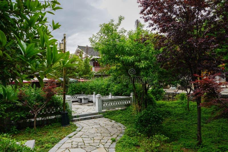 Stenbana i trädgård för tegelplatta-taklade byggnader på molnig spri royaltyfri fotografi