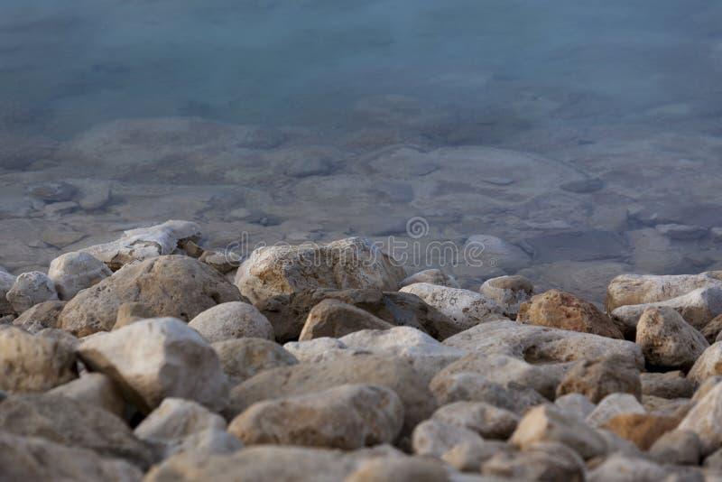 Stenblock på kanten för blått vatten arkivfoto