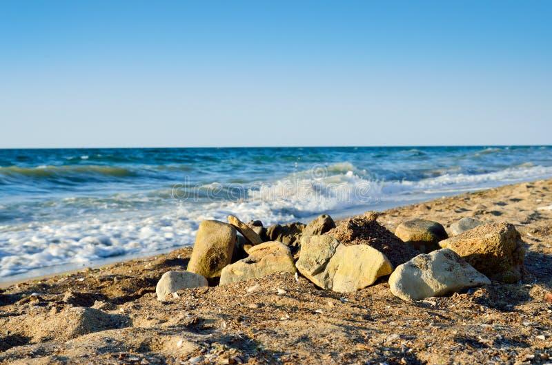 Stenblock på stranden, mot den tidvattens- tråkmånsen av havet arkivbild