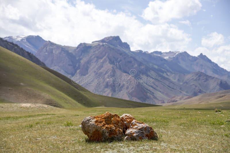 Stenblocket som täckas med laven på, betar mot den blåa himlen med moln och bergskedjor Resor kyrgyzstan arkivfoto