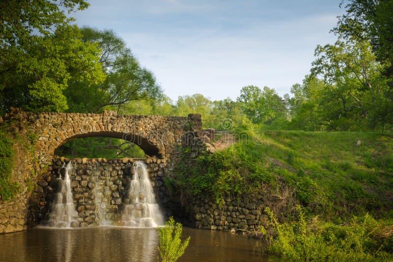 Stenbro och vattenfall i Reynolda trädgårdar royaltyfri fotografi