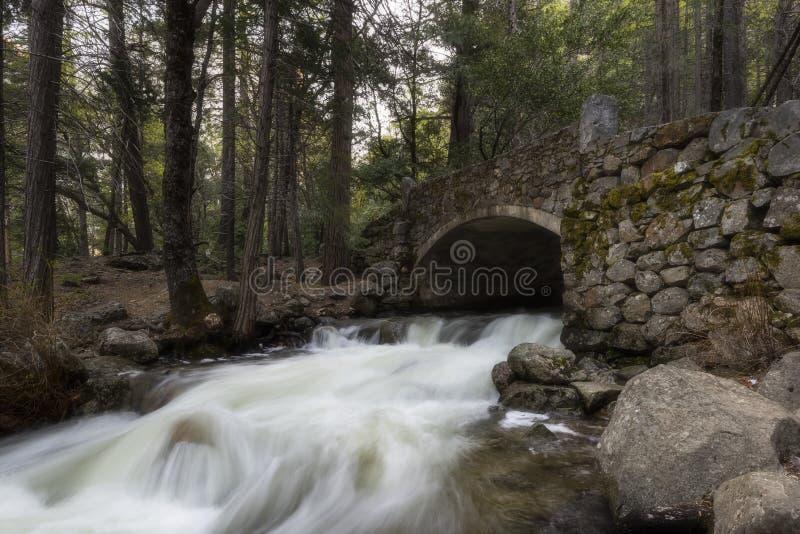 Stenbro och vattenfall under Bridalveil nedgångar, Yosemite nationalpark, Kalifornien arkivfoto
