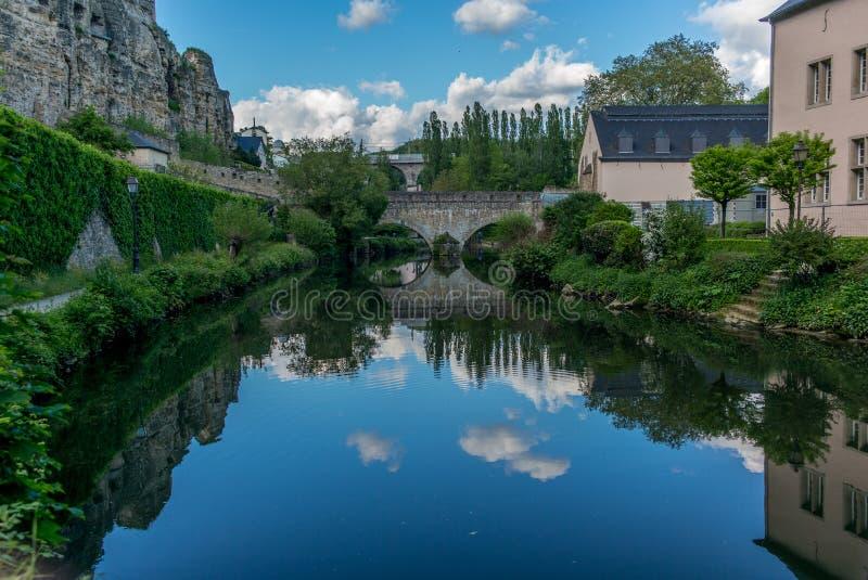 Stenbro som reflekterar i den Alzette floden royaltyfria foton