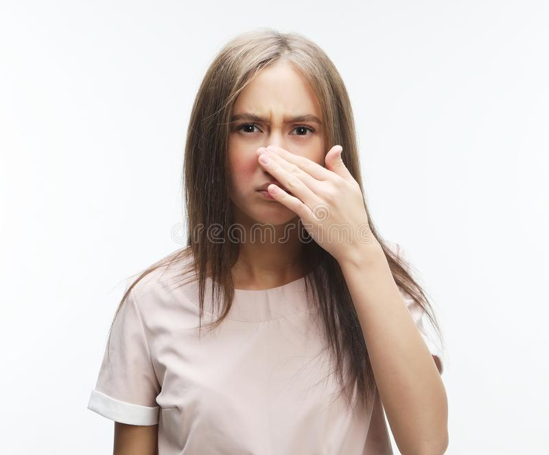 The stench. Closes the woman`s nose. Over white background royalty free stock image