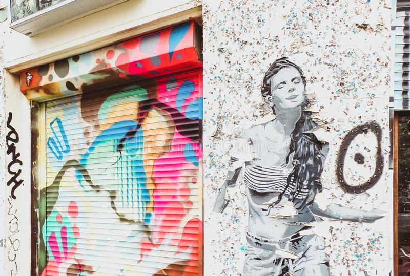 Stencil Art of Woman on Wall Near Door Shutter With Graffiti royalty free stock photography