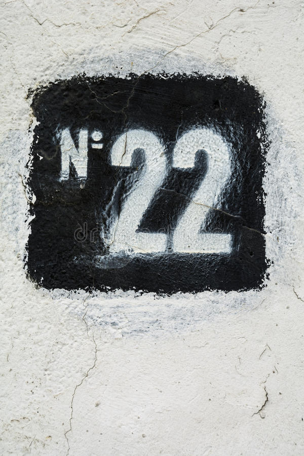 Stencilled number twenty two in black on white plaster wall royalty free stock image