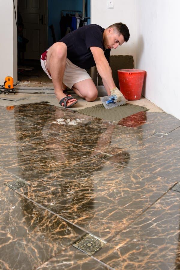 Stenditura delle piastrelle di ceramica mentre riparando nella sala ed applicare colla al pavimento fotografie stock
