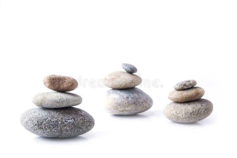 Stenen bovenop elkaar worden gestapeld en evenwichtig op het wit dat royalty-vrije stock fotografie