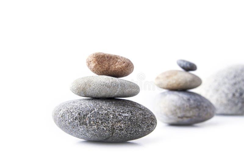 Stenen bovenop elkaar worden gestapeld en evenwichtig op het wit dat stock afbeelding