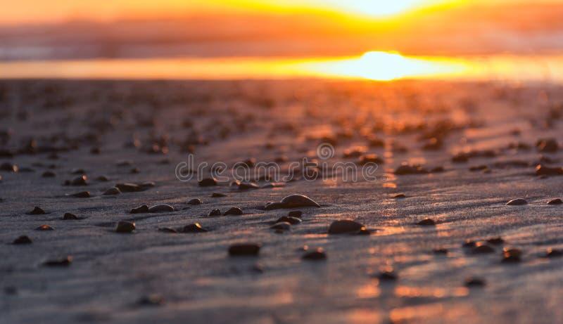 Stenen in de zonsondergang op een strand royalty-vrije stock afbeelding