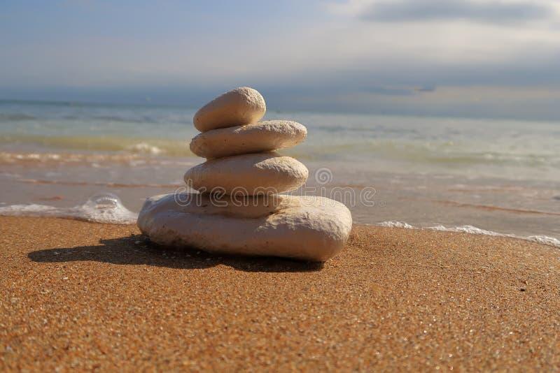 Stenen die bovenop elkaar op een zandig strand worden opgestapeld stock afbeelding