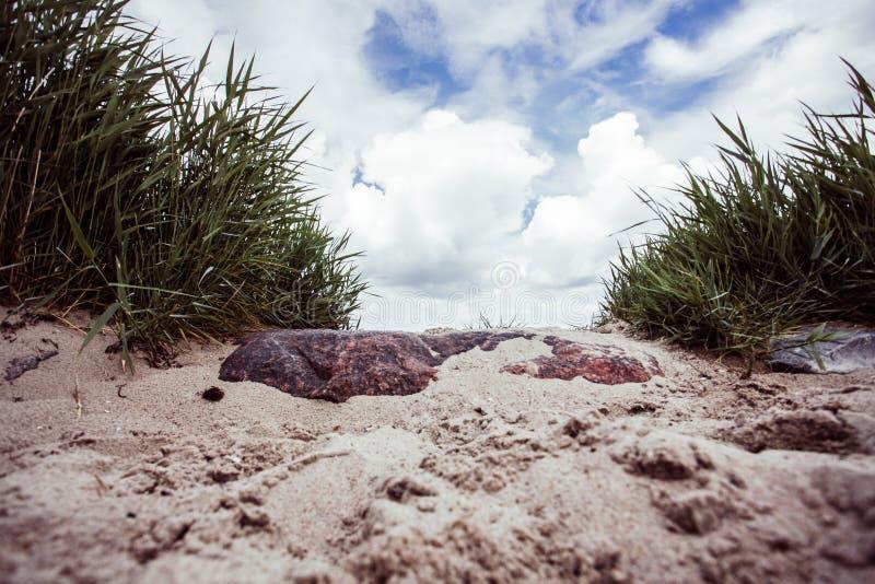 Stenen die door gras en de hemel worden ontworpen royalty-vrije stock fotografie