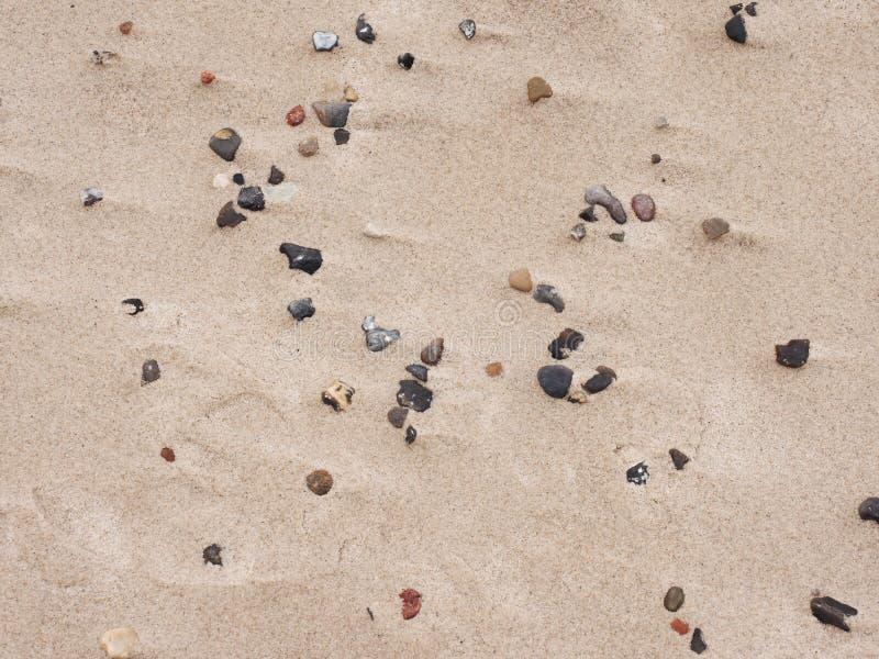Stenen en kiezelstenen in zand van strand Romantische gang voor de kust royalty-vrije stock afbeeldingen