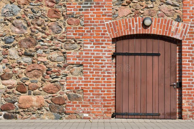 Stenen en rode bakstenen muur met houten deur royalty-vrije stock afbeeldingen