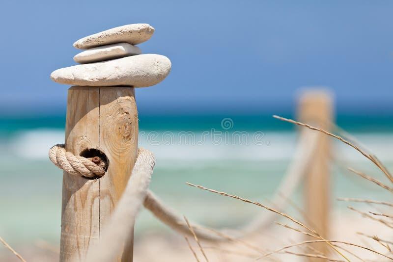 Stenen evenwichtig op houten leuning dichtbij het strand. royalty-vrije stock foto