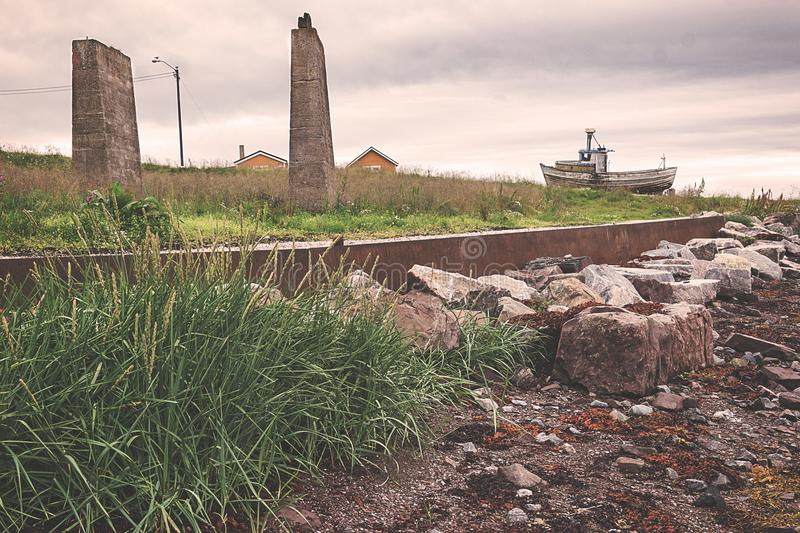Stenen fördärvar och ett gammalt fartyg på kusten royaltyfria bilder