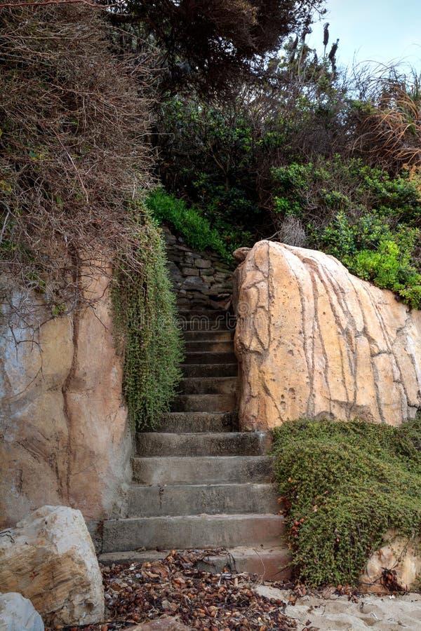 Stenen kliver att leda in i en alkov som finnas på en Kalifornien strand royaltyfri foto